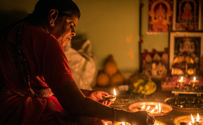 women decorating home on karthigai deepam festival