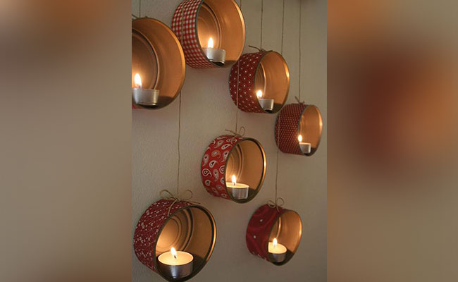 Painted metal tins with diwali diyas hanged on the wall